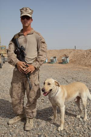 Maxx, an improvised explosive device detector dog, stands next to his handler, Lance Cpl. Stephen Mader, at Combat Outpost Paserlay, July 26, 2012. Mader, with 3rd Battalion, 8th Marines, Regimental Combat Team 6, volunteered to go through a 5-week school in the States to work with IDDs. He's an infantry mortarman by trade, but deployed to use Maxx to help sniff out IEDs and other explosive before they can damage vehicles or Marines.